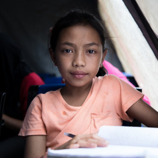 10-year old Aisah* studies in a Save the Children temporary learning centre after her school was destroyed during the conflict in Marawi City, the Philippines.
