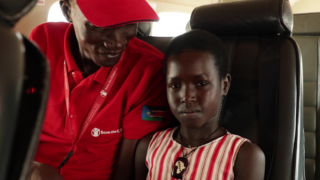 Save the Children Case Worker, Zacharia Manyang, making Asha* comfortable on the way to meet her mother after 5 years of separation